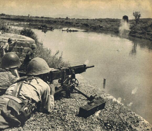 A Japanese soldier firing a Type 92 Heavy Machine Gun across the Miluo river in September 1941