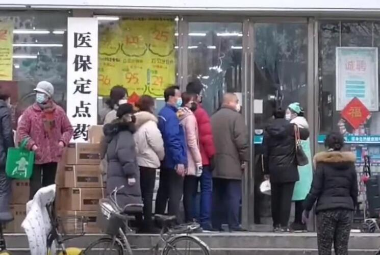 Citizens of Wuhan lining up outside of a drug store to buy masks during the Wuhan coronavirus outbreak Image